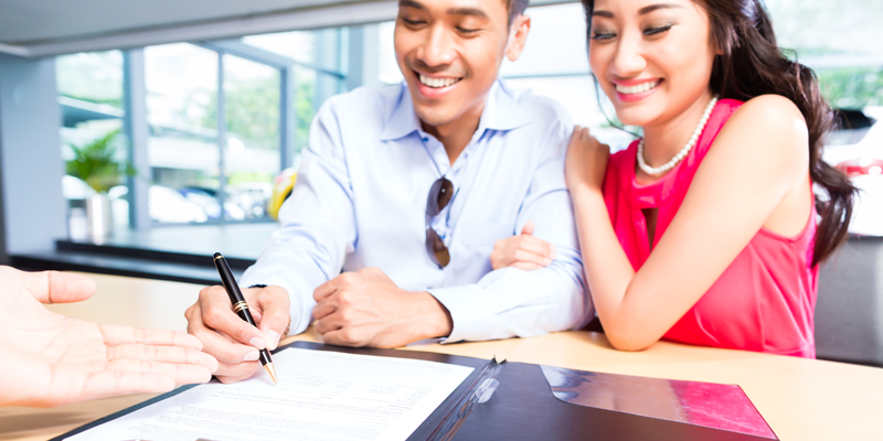 Young Couple Signing Contract at Car Dealership