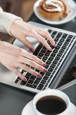 Woman's hands typing on a laptop keyboard with coffee and fresh cake